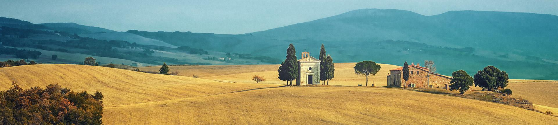 golden tuscan hills with stone house and small church