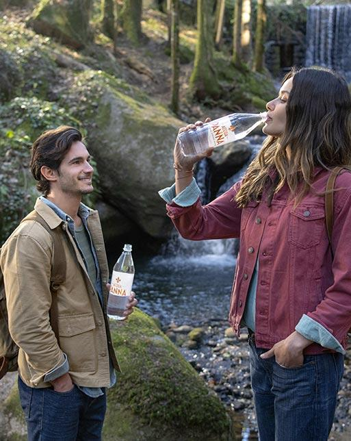 Boy and Girl Drinking Acqua Panna Natural Mineral Water On Journey