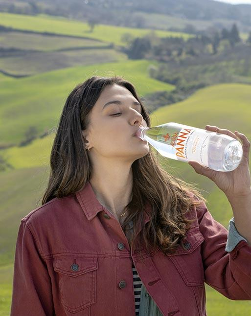 Girl Drinking Acqua Panna Natural Mineral Water On Hills